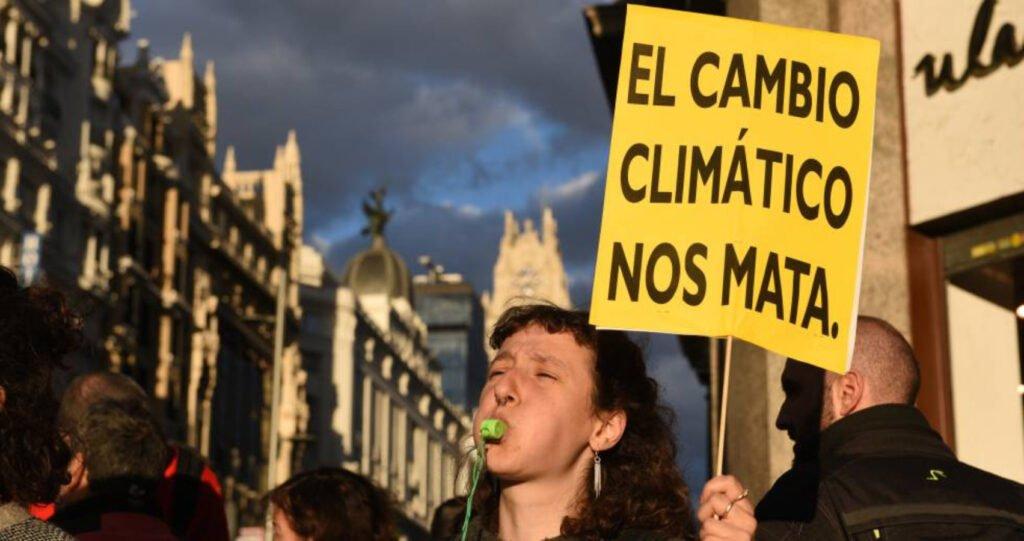 Mujer con pancarta del cambio climático.