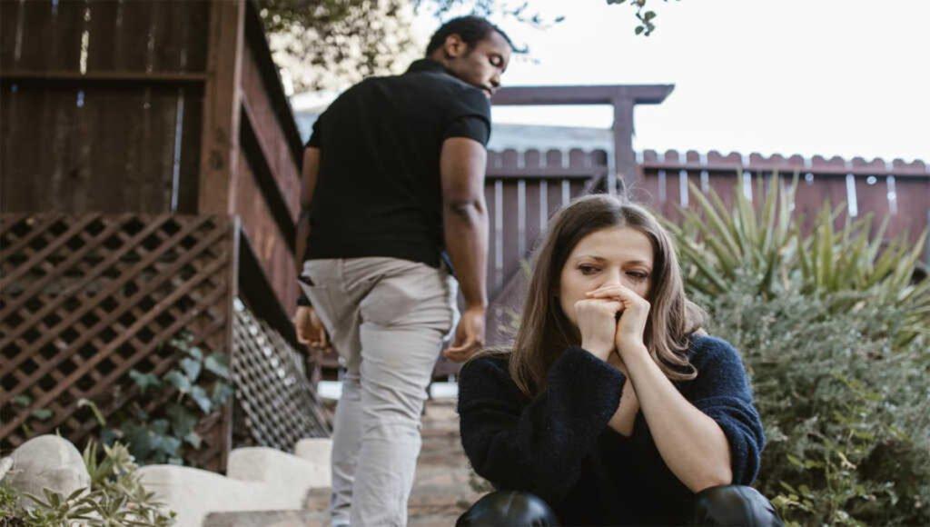 Mujer llorando y su pareja ignorandola. Ejemplo de gaslighting.