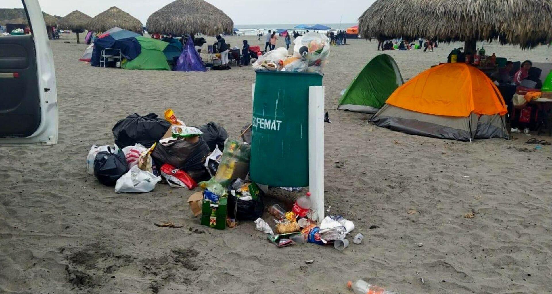 bote de basura verde con bolsas de plástico en el interior y fuera sobre la arena de la playa; detrás hay tiendas de acampar de colores bajo palapas