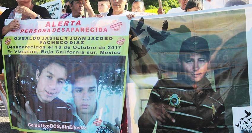 Personas sostienen mantas con foto de personas desaparecidas en Baja California Sur. DEsapariciones en México.