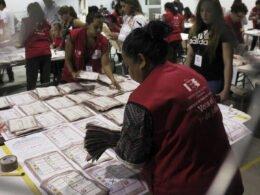 Señora con chaleco color rojo viendo hacia una mesa color blanco y papeletas de elecciones.