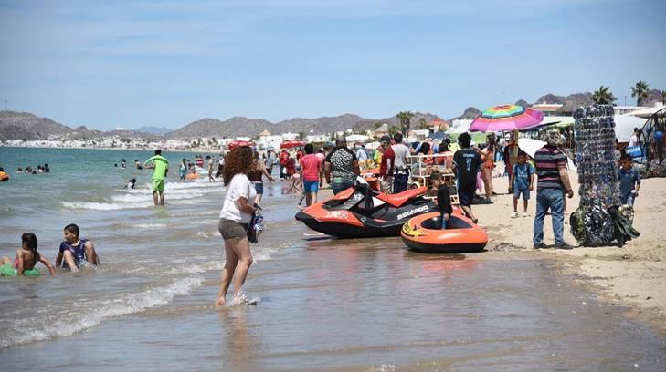 Imagen de turistas en la playa y dentro del mar en Sonora.