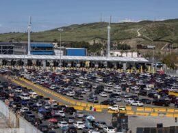Linea de la frontera de Tijuana. En medio hay una línea color amarillo fuerte y por los dos lados se encuentran diversidad de carros