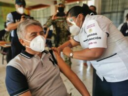 Señor adulto mayor con cubrebocas color blanco, camisa color gris claro con negro, recibe vacunacion de una señora que tiene filipina color blanco, careta y cubreboca color blanco.