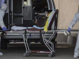 Hombre en camilla saliendo de ambulancia. Dos hombres con traje color blanco, guantes azules y mascara color blanco.