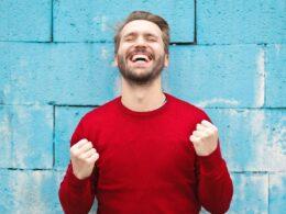 hombre con barba viste sudadera roja y sonríe con los ojos cerrados