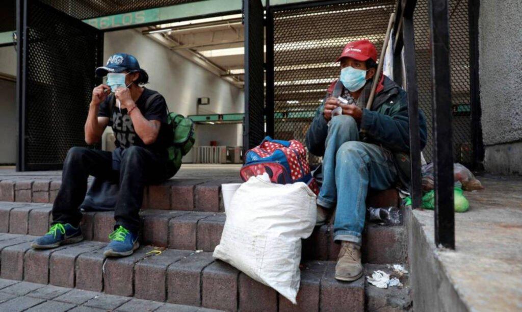 Dos hombres sentados en escalones: el hombre de la derecha tiene una gorra color roja, cubreboca color azul y pantalon de mezclilla. Del lado izquierdo, un hombre tiene gorra color azul con letras color blanco, cubrebocas azul, camisa y pantalón color negro.