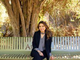 mujer de cabello largo sentada sobre una banca; detrás un árbol
