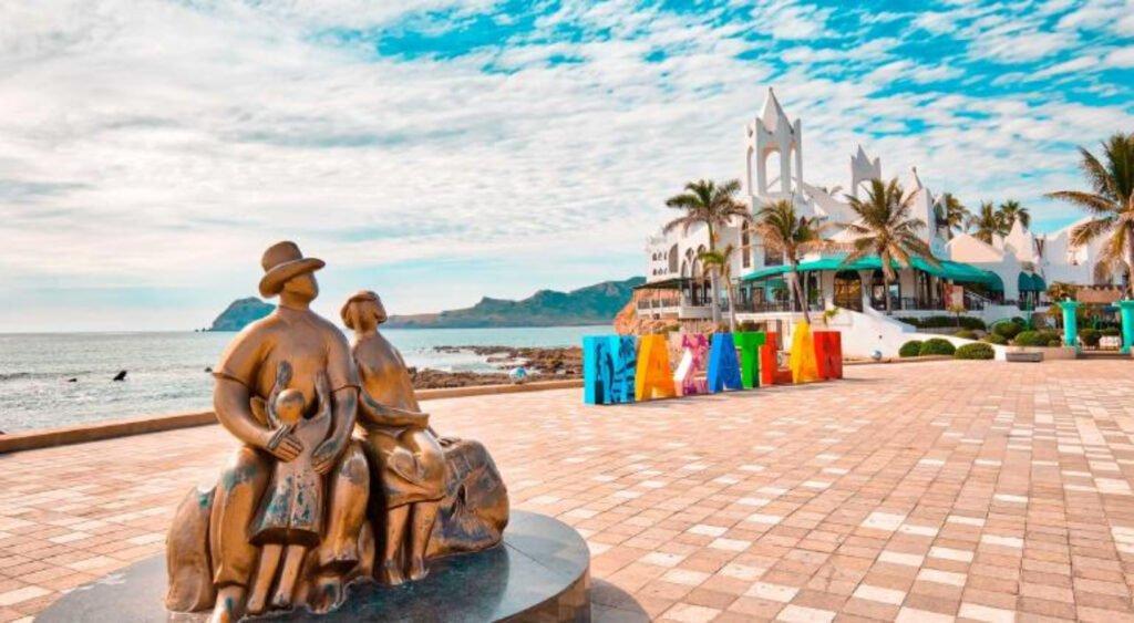En el centro se encuentran las letras que forman la palabra MAZATLAN, cada uno de diversos colores. En la parte derecha se encuentra una estructura color blanco y en el fondo el mar. Del lado izquierdo se encuentra un monumento color bronce de una pareja con una hija.