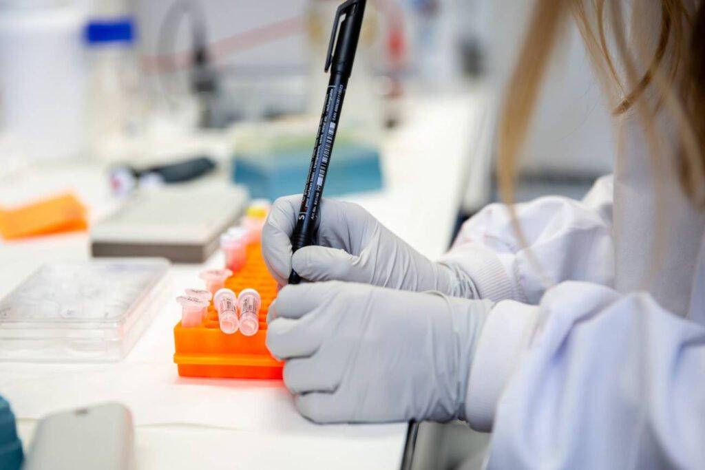 Mujer con bata de laboratorio color blanca y guantes color gris claro; en la mano derecha tiene un plumón de color negro y esta escribiendo en tubos pequeños transparentes.