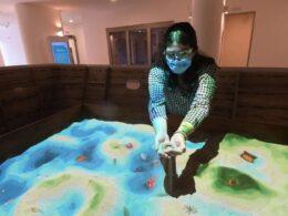 mujer sostiene arena entre sus manos dentro de un museo