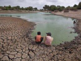 Dos niños se encuentran frente a agua. El niño del lado derecho tiene una gorra color negro y camisa naranja claro. El niño del lado izquierdo tiene una camisa color naranja y pantalon negro.