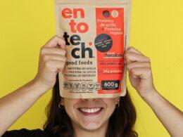 Foto de mujer sonriendo sosteniendo una bolsa de proteína de entotech