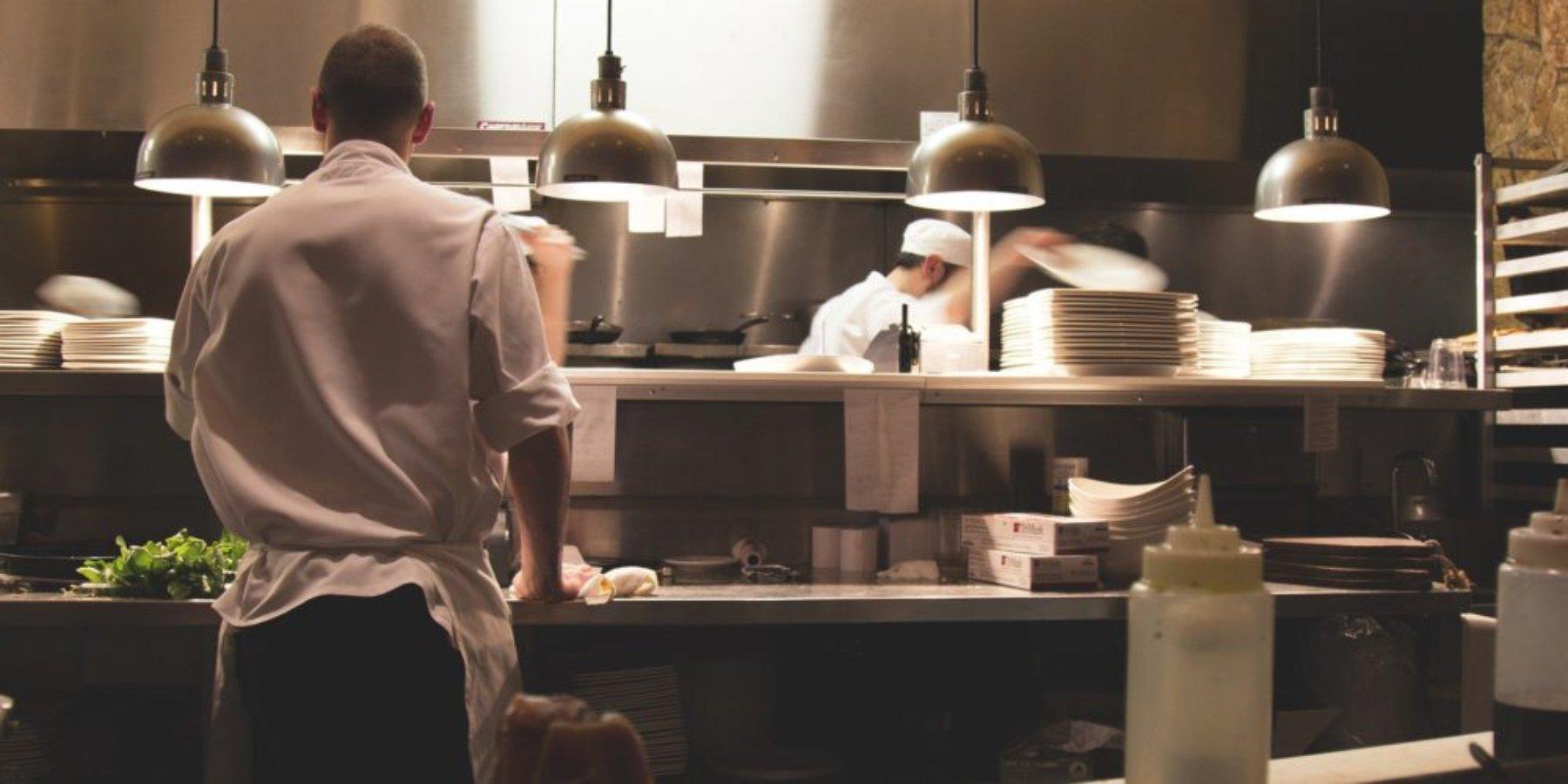 Imagen de restaurante en la cocina donde hay 4 lamparas colgantes de color metal, mesas de acero inoxidable y una persona parada con camisa de color blanco y pantalon negro.   Gas natural