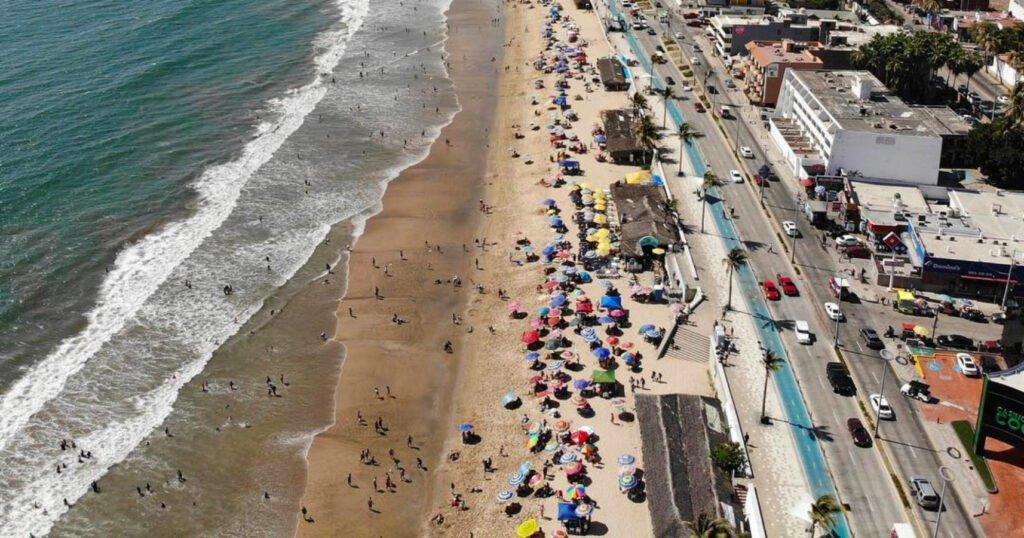 Derrama económica en Mazatlán. Del lado izquierdo se encuentra el mar y arena. Se puede notar una gran variedad de sombrillas. Del lado derecho se encuentra la carretera con variedad de carros y edificios.