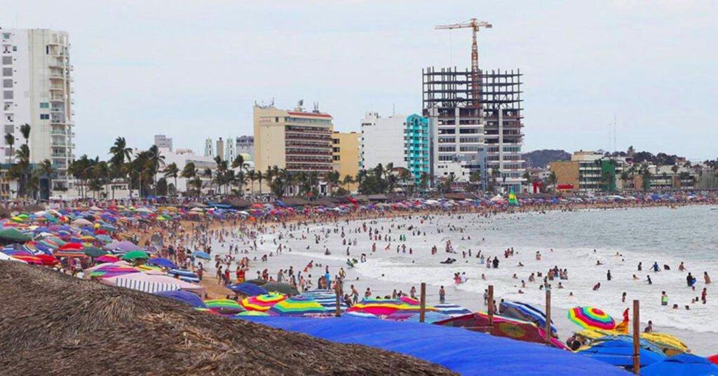 En el centro se puede observar una variedad de sombrillas de diferentes colores. Atras se notan tres edicios grandes y del lado derecho esta el mar. Derrama económica de Mazatlán.