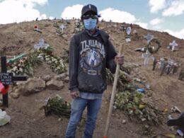 hombre con sudadera que dice Tijuana, gorra y cubrebocas sostiene un palo en medio del cementerio