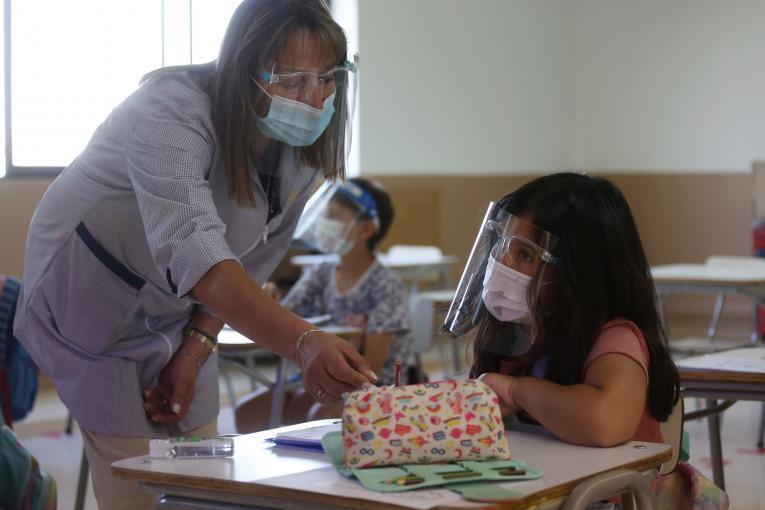 Docente con alumno y equpo de protección por pandemia.