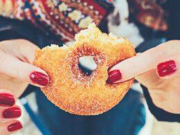 mano con uñas rojas sostiene dona cubierta de azúcar