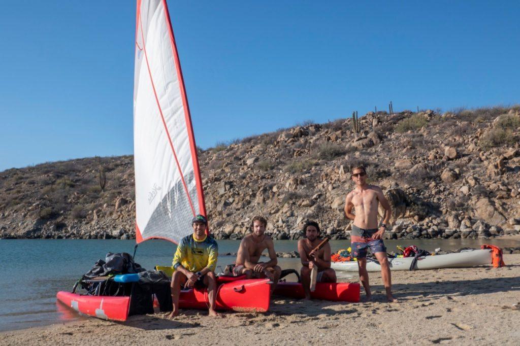 personas al lado de un kayak sobre la playa