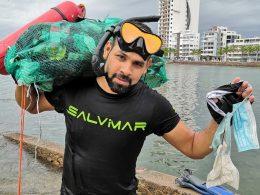 Hombre con visores y esnorquel carga bultos con basura salida del mar