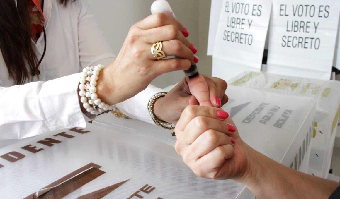 PREP 202Mano coloca tinta en el dedo a persona para emitir su voto en México