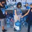 tres personas alrededor de un garrafón de agua en el Aguatón