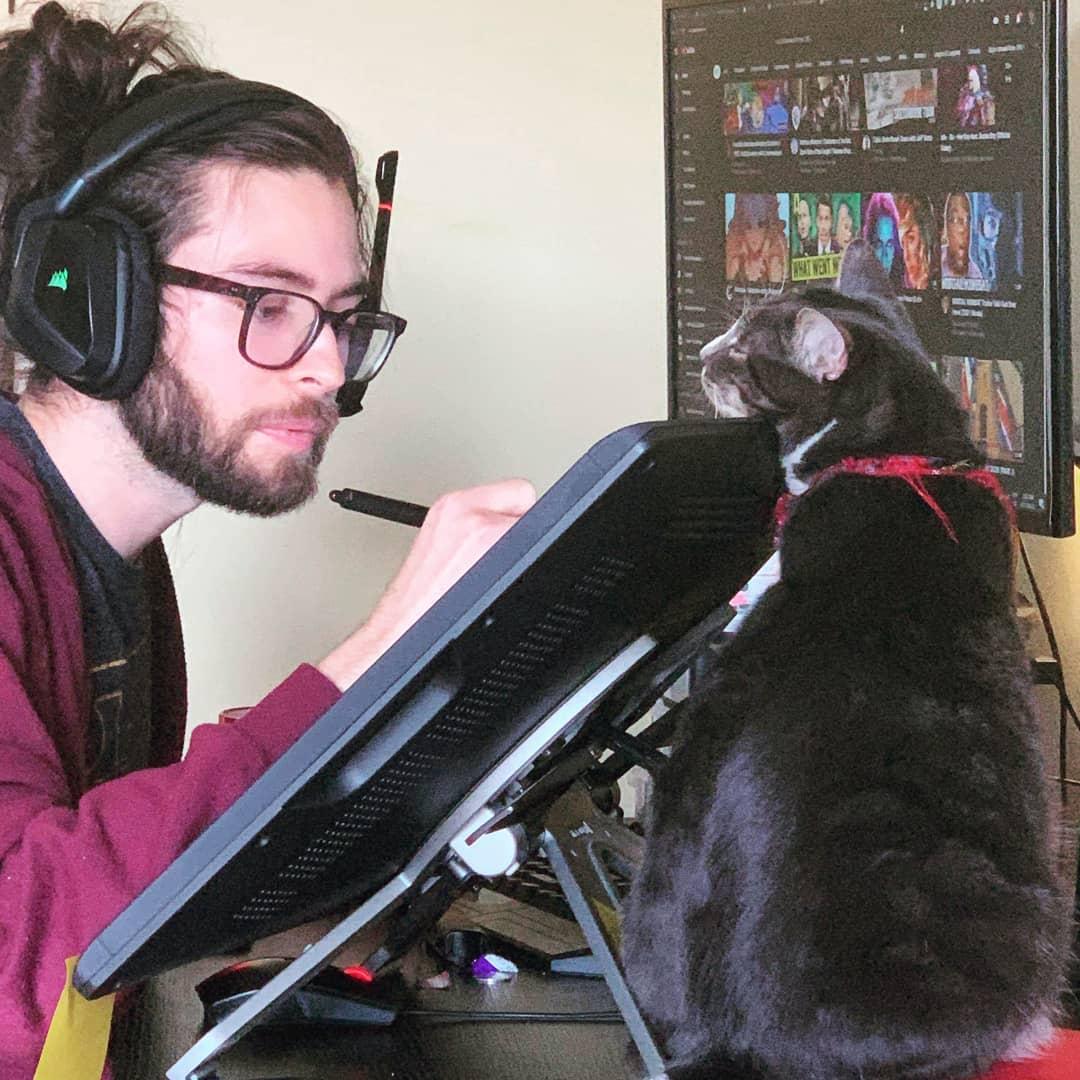 Luis de la Rosa trabajando con su gato a lado.
