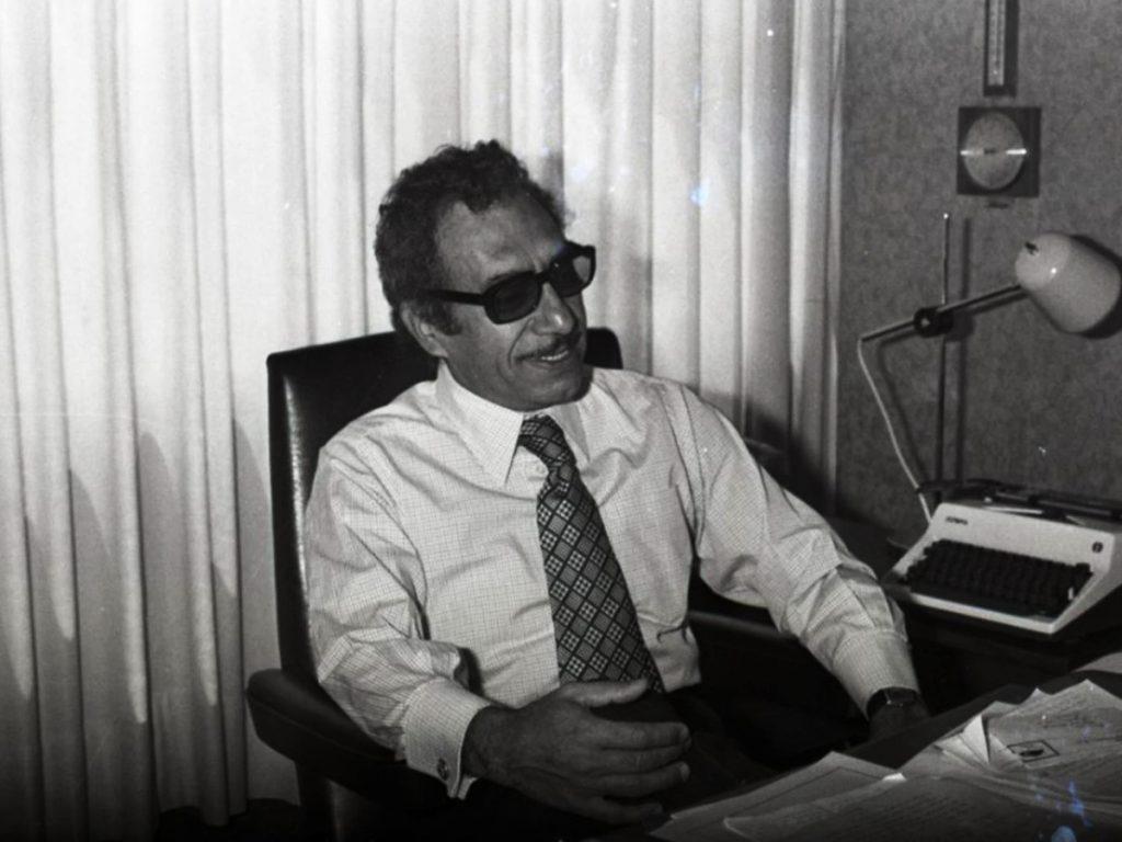 Manuel Buendía en su escritorio junto a máquina de escribir, con lentes obscuros y sonriendo.