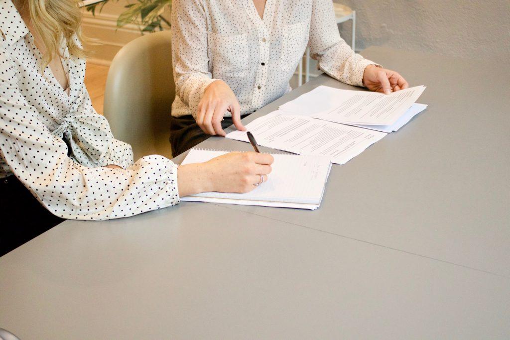 Firma de contrato sobre mesa blanca.