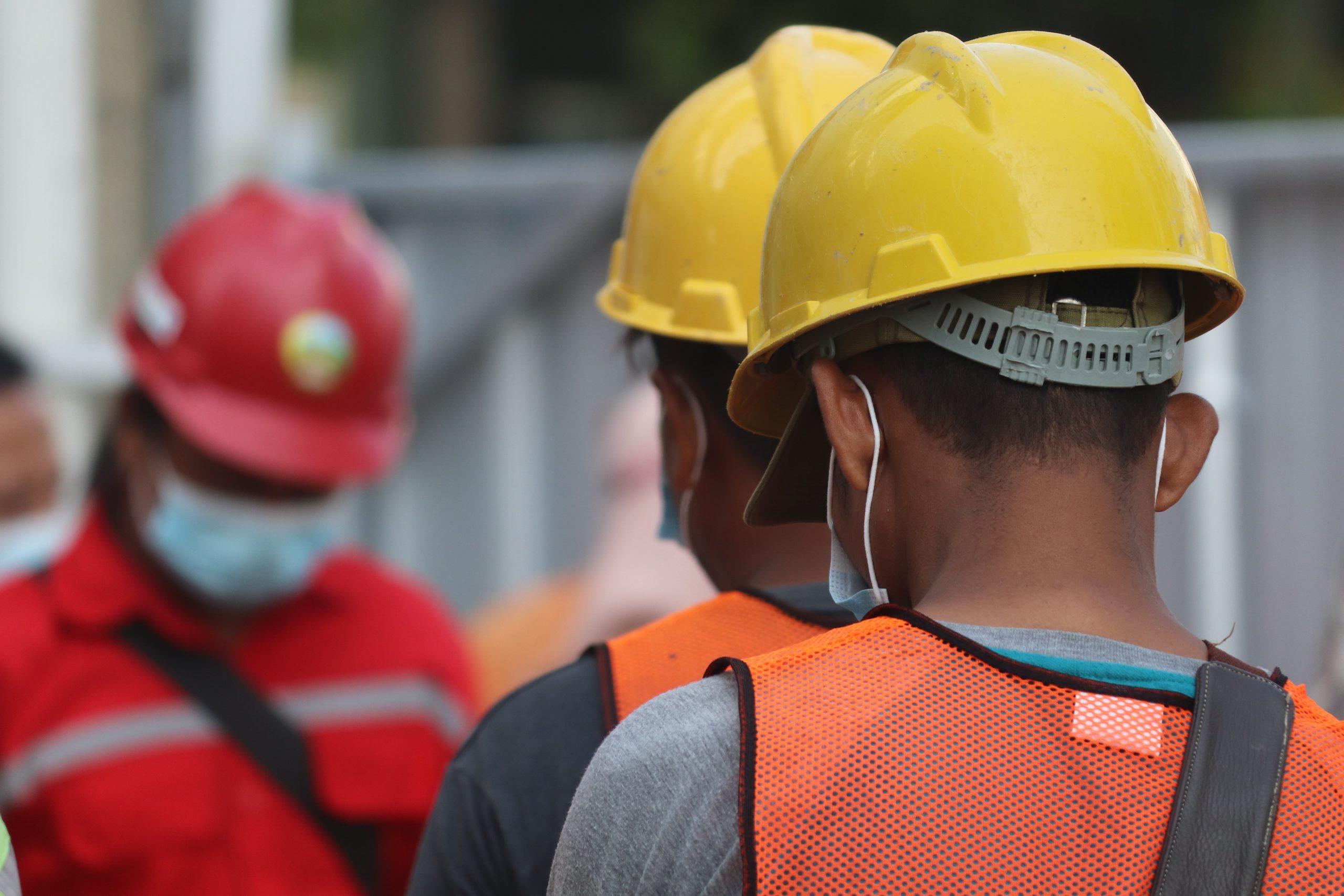 Trabajadores de espalda con cascos de construcción.