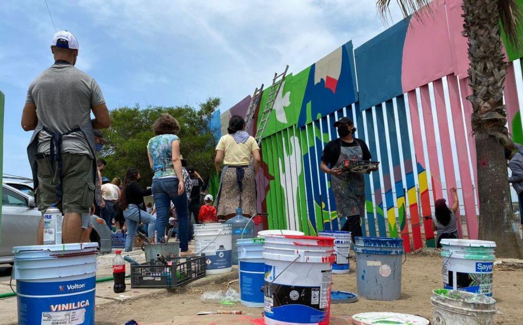 Artistas locales de Tijuana pintando muro fronterizo.