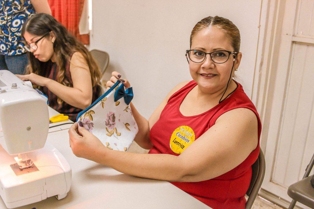 Alumna de Café Costura Hermosillo frente a máquina de costura sostiene bolsa de tela.