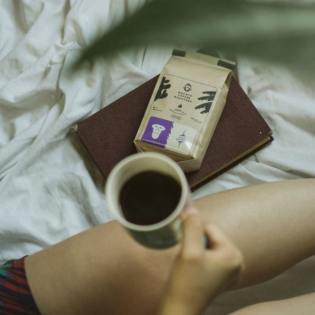 Taza de café con bolsa de café Macaco en el fondo sobre libro en cama.