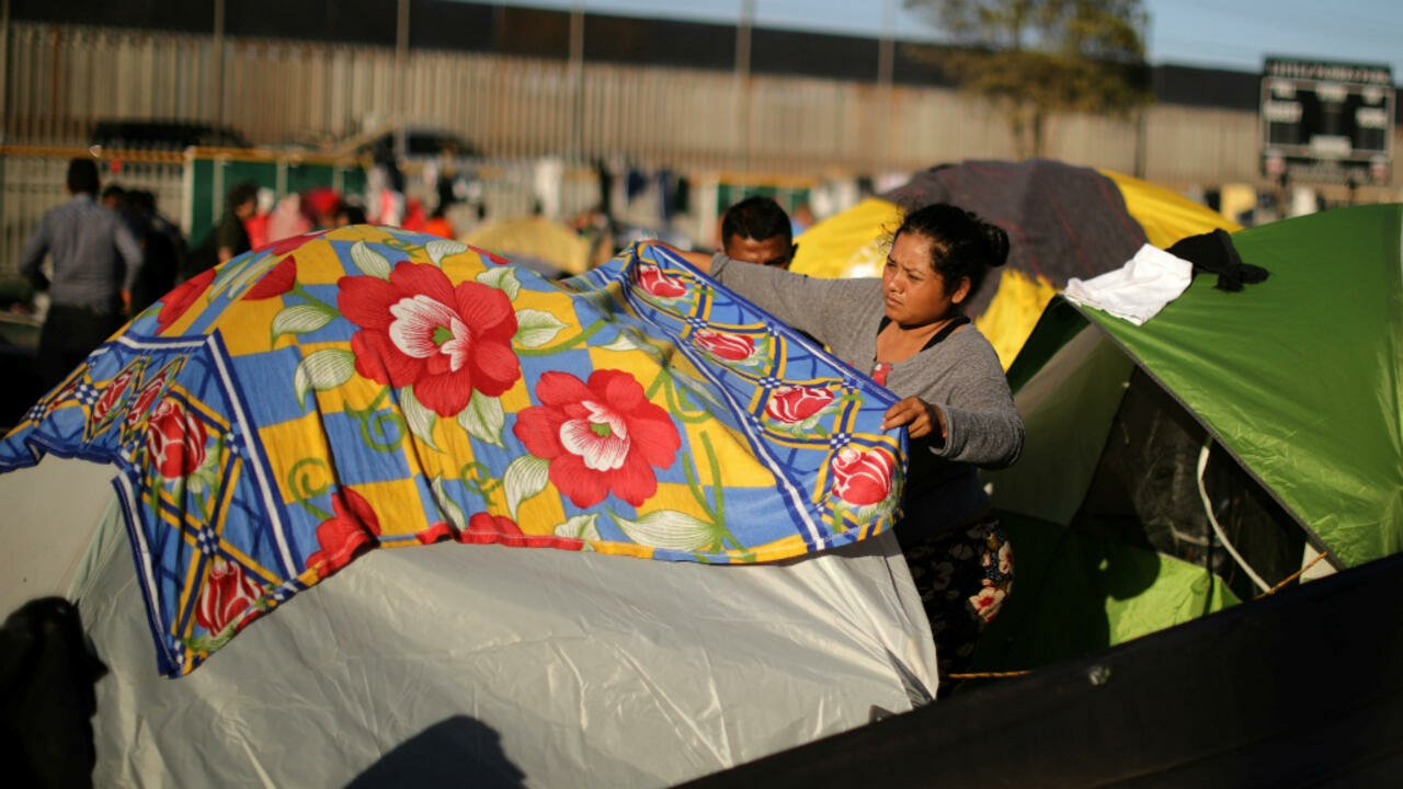 Una mujer, que hace parte de la caravana migrante, cubre su tienda de campaña en el refugio provisional en Tijuana.