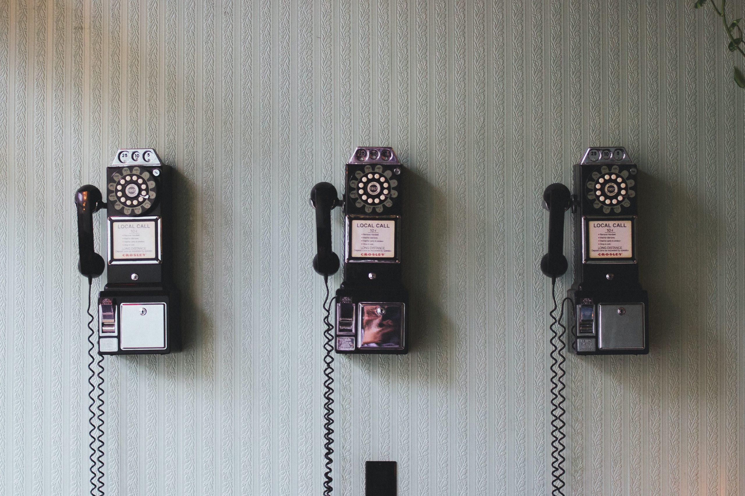 Tres teléfonos en la pared representando a la comunidad no binaria.
