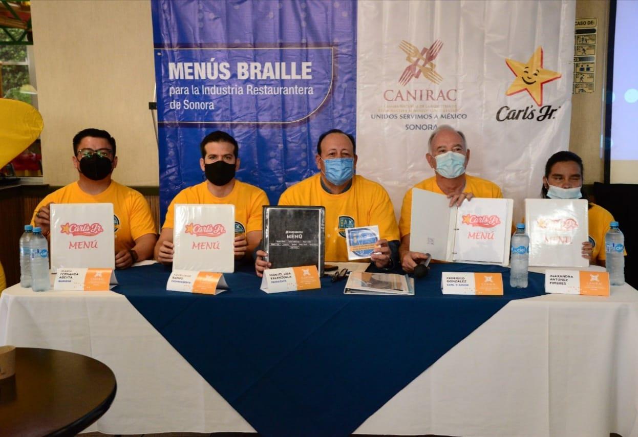 Miembros de CANIRAC presentan menú en braille para Carl 's JR.