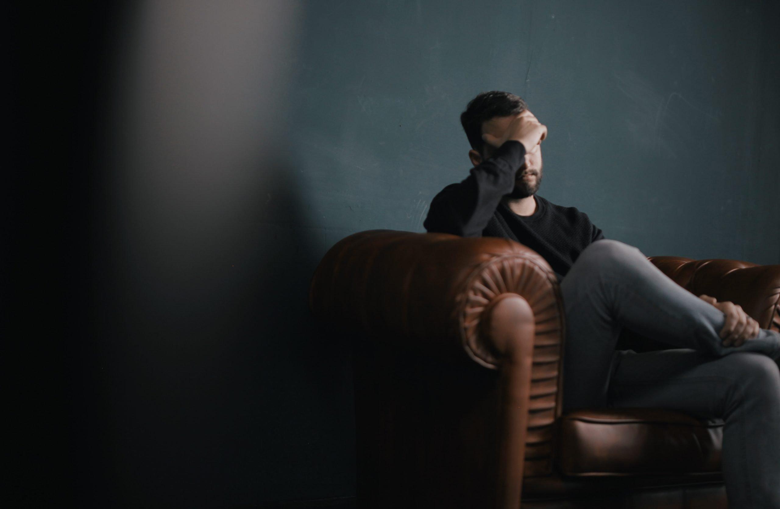 Hombre con cara de preocupación en sillón.